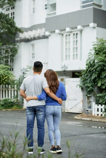 Rear view of young hugging couple standing outdoors and looking at big mansion